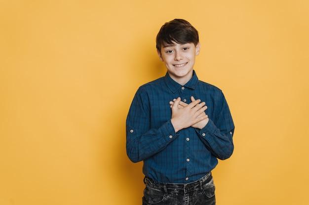 Il giovane bel ragazzo vestito casual con occhi marroni e ampio sorriso incrociò le mani sul petto esprimendo amore e felicità su sfondo giallo. concetto di felicità e amore.