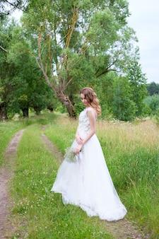 Giovane bella sposa in abito da sposa bianco all'aperto, trucco e acconciatura