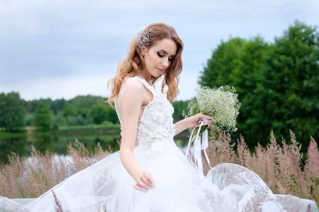 Giovane bella sposa in abito da sposa bianco all'aperto
