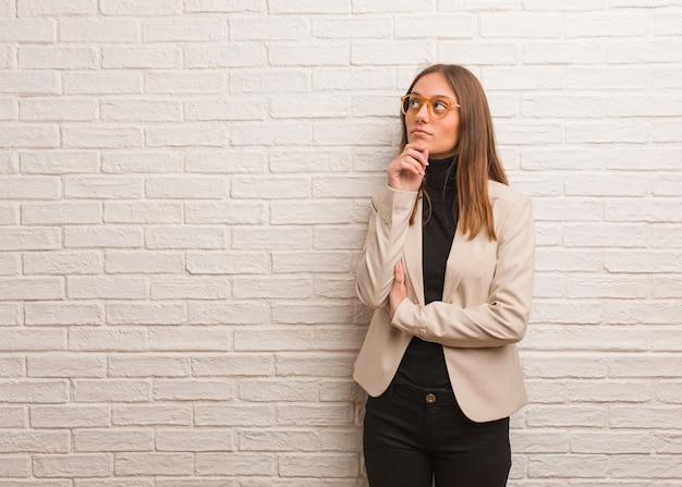 Giovane donna graziosa dell'imprenditore di affari che dubita e confusa