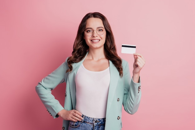 La giovane signora graziosa di affari dimostra la carta di credito su fondo rosa