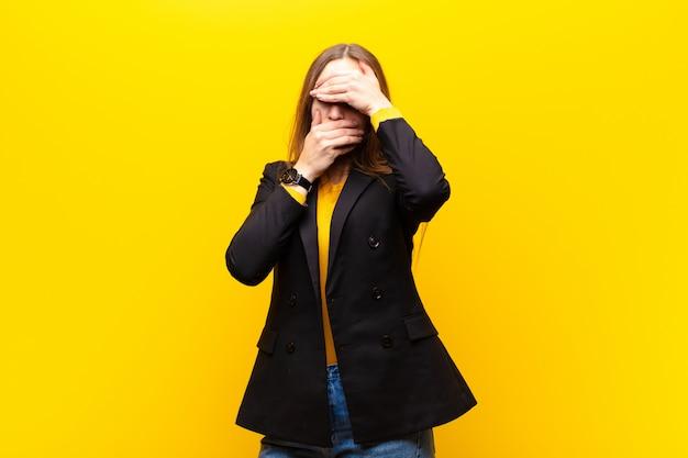 Giovane imprenditrice carina che copre il viso con entrambe le mani dicendo no alla telecamera! rifiutare le immagini o vietare le foto su sfondo arancione