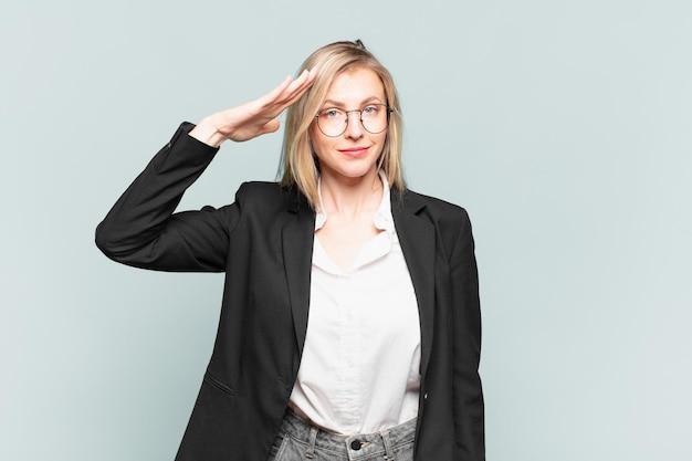 Giovane bella donna d'affari che saluta la telecamera con un saluto militare in un atto di onore e patriottismo, mostrando rispetto