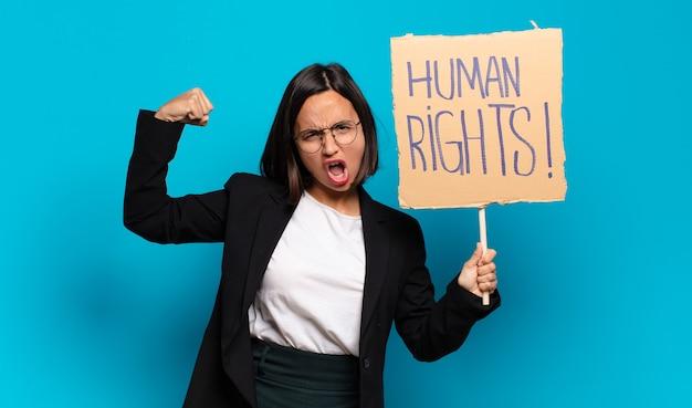 Giovane bella donna di affari che tiene cartello con testo: diritti umani. concetto di attivista