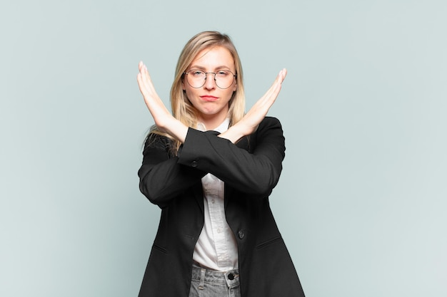 Giovane bella donna d'affari che sembra infastidita e stanca del tuo atteggiamento, dicendo basta! mani incrociate davanti, dicendoti di fermarti