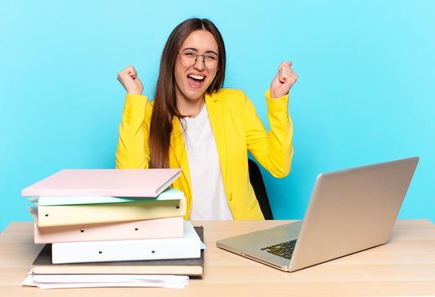 Giovane donna di affari graziosa che sembra estremamente felice e sorpresa, celebrando il successo, gridando e saltando
