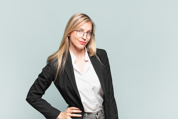 Giovane bella donna d'affari che sembra orgogliosa, sicura di sé, fresca, sfacciata e arrogante, sorridente, sentendosi di successo