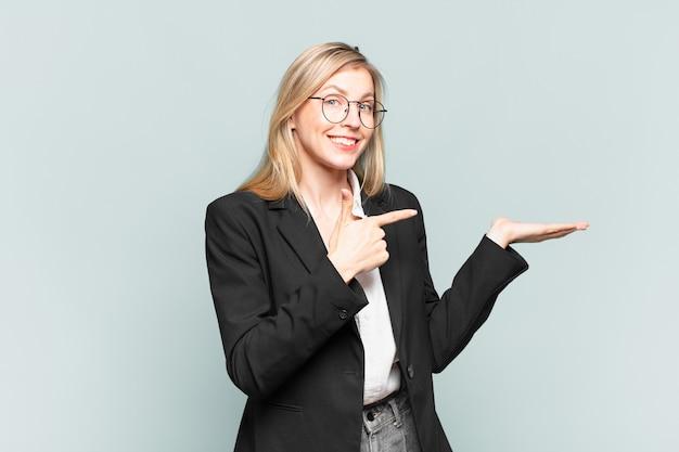 Giovane bella donna d'affari che sorride allegramente e indica lo spazio della copia sul palmo sul lato, mostrando o pubblicizzando un oggetto