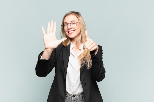 Giovane bella donna d'affari sorridente e dall'aspetto amichevole, mostrando il numero sei o il sesto con la mano in avanti, conto alla rovescia