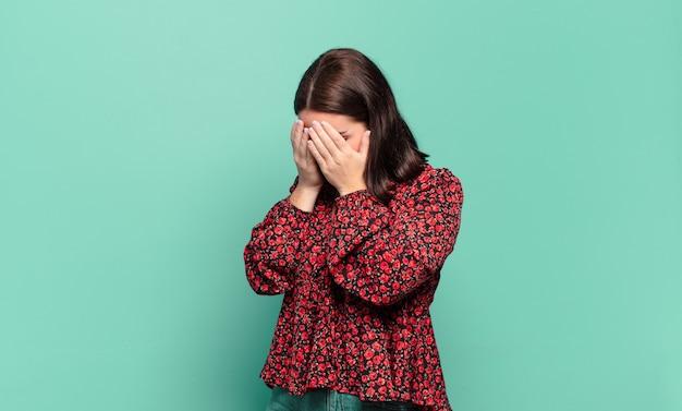 Giovane donna abbastanza casual che copre gli occhi con le mani con uno sguardo triste e frustrato di disperazione, pianto, vista laterale