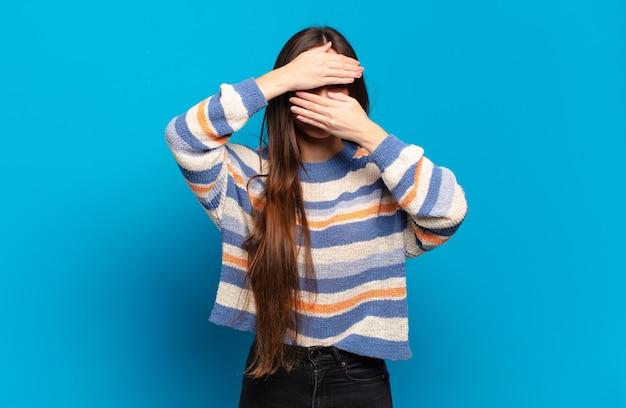 Giovane donna abbastanza casuale che copre il viso con entrambe le mani dicendo no alla fotocamera! rifiutare le immagini o vietare le foto