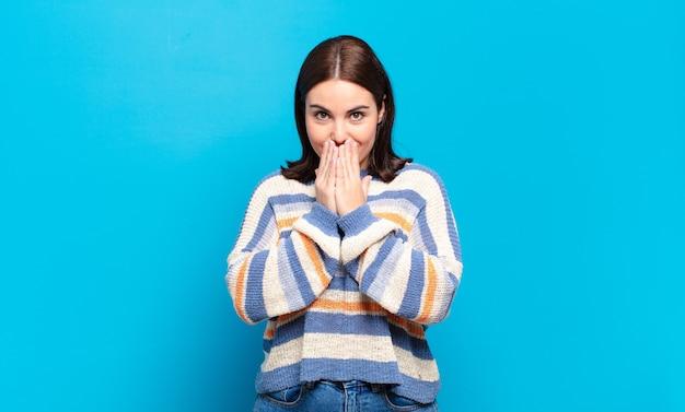 Giovane donna abbastanza casual felice ed eccitata, sorpresa e stupita che copre la bocca con le mani, ridendo con un'espressione carina
