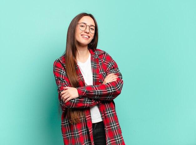Giovane donna abbastanza casual che ride felice con le braccia incrociate, con una posa rilassata, positiva e soddisfatta