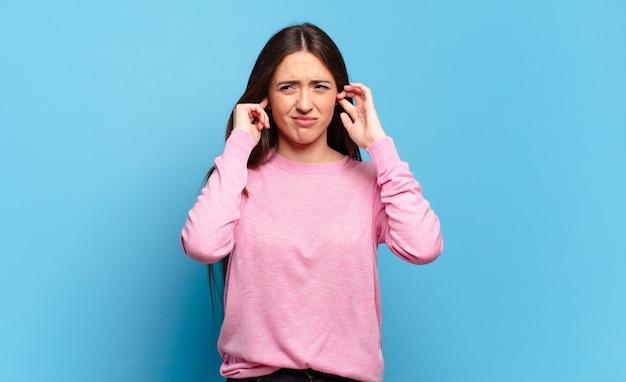 Giovane donna piuttosto casual che sembra arrabbiata, stressata e infastidita, coprendo entrambe le orecchie con un rumore assordante, un suono o una musica ad alto volume