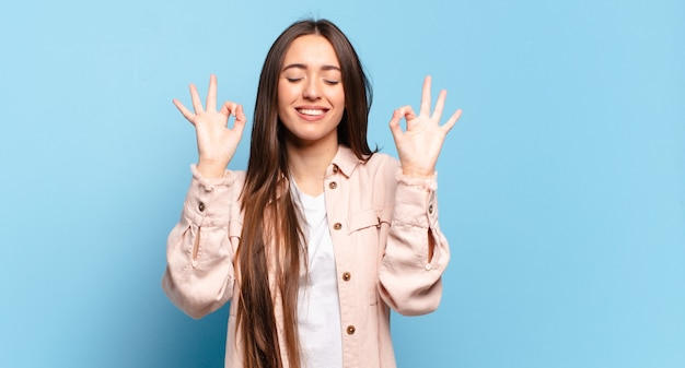Giovane donna piuttosto casual che sembra concentrata e medita, si sente soddisfatta e rilassata, pensa o fa una scelta