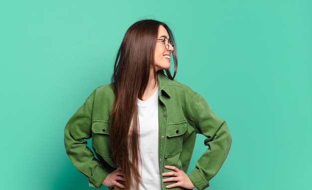 Giovane donna abbastanza casual che sembra felice, allegra e sicura di sé, sorride con orgoglio e guarda dalla parte con entrambe le mani sui fianchi