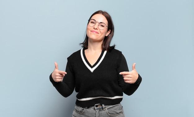 Giovane donna piuttosto casual che sembra orgogliosa, arrogante, felice, sorpresa e soddisfatta, indicando se stessa, sentendosi come una vincitrice