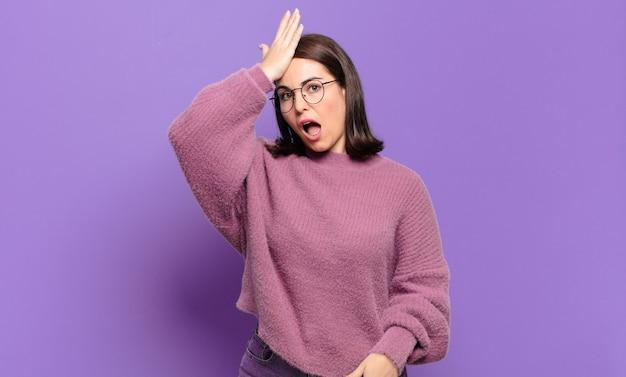 Giovane donna piuttosto casual che alza il palmo della mano sulla fronte pensando oops, dopo aver commesso uno stupido errore o ricordando, sentendosi stupido