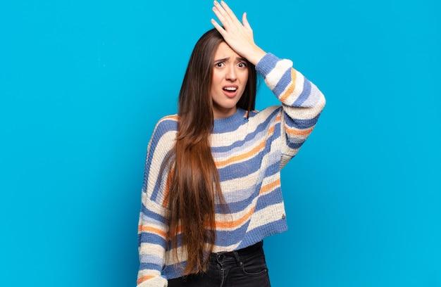 Giovane donna piuttosto casual che alza il palmo alla fronte pensando oops, dopo aver commesso uno stupido errore o ricordando, sentendosi stupido