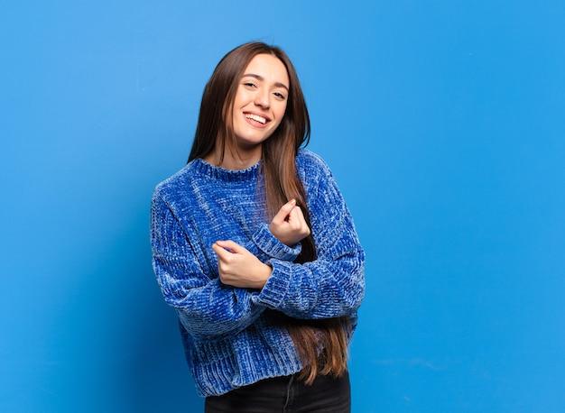 Giovane donna abbastanza casual che sorride allegramente e festeggia, con i pugni serrati e le braccia incrociate, sentendosi felice e positiva