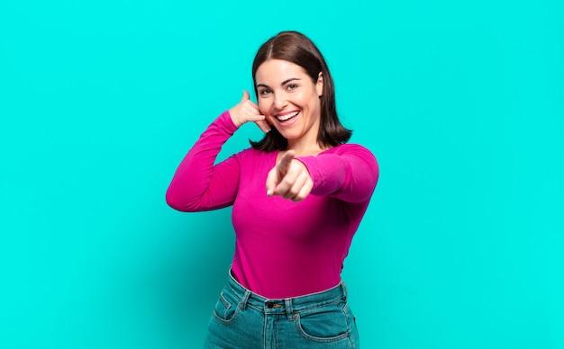 Giovane donna abbastanza casual che sorride allegramente e indica la macchina fotografica mentre ti fa una telefonata dopo un gesto