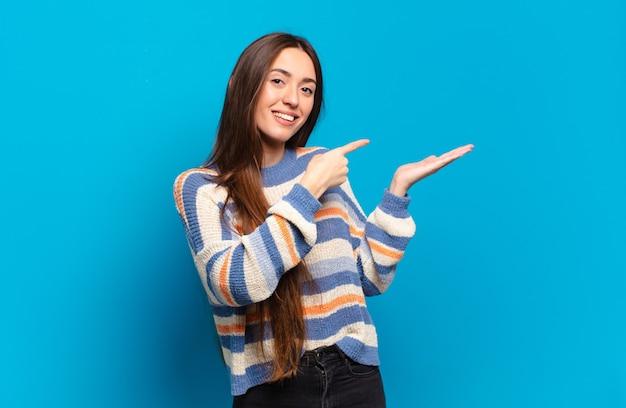 Giovane donna abbastanza casual che sorride allegramente e indica lo spazio della copia sul palmo sul lato, mostrando o pubblicizzando un oggetto
