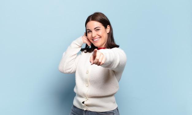 Giovane donna abbastanza casual che sorride allegramente e punta in avanti mentre effettua una chiamata in seguito gesto, parlando al telefono