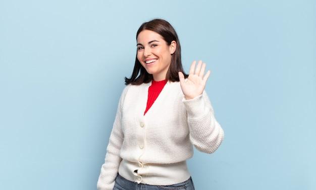 Giovane donna abbastanza casual che sorride allegramente e allegramente, agitando la mano, dandoti il benvenuto e salutandoti o salutandoti