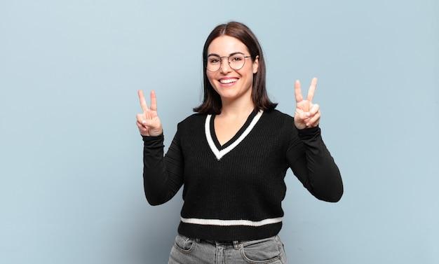 Giovane donna abbastanza casuale che sorride e che sembra felice, amichevole e soddisfatta, gesticolando vittoria o pace con entrambe le mani