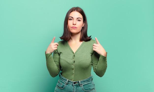 Giovane donna piuttosto casual con un cattivo atteggiamento che sembra orgogliosa e aggressiva, che punta verso l'alto o che fa un segno divertente con le mani