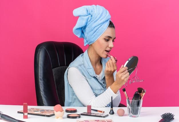 Giovane donna abbastanza caucasica con i capelli avvolti in un asciugamano seduto al tavolo con strumenti per il trucco che tengono e guardano lo specchio applicando il rossetto isolato sulla parete rosa con lo spazio della copia