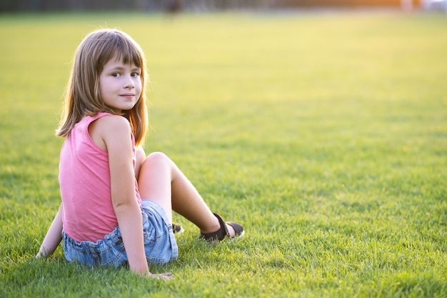 Ragazza giovane e carina che si siede sul prato di erba verde fresca in una calda giornata estiva all'aperto.