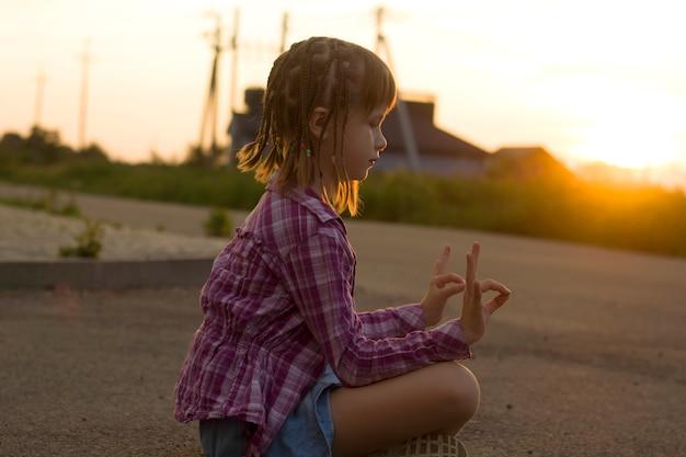 Ragazza giovane bambino grazioso con trecce divertenti allenamento yoga esercizio da solo all'aperto su sfondo rurale nebbioso all'alba o al tramonto.