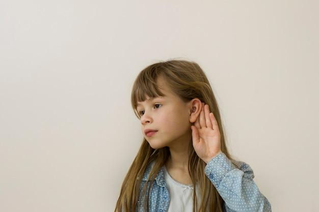 Giovane ragazza graziosa del bambino con capelli sciolti lunghi, occhi sognanti e espressione seria del viso in ascolto su sfondo chiaro.