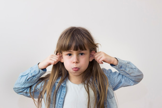 Giovane ragazza graziosa del bambino con i capelli sciolti lunghi che scherzano facendo l'espressione divertente del fronte