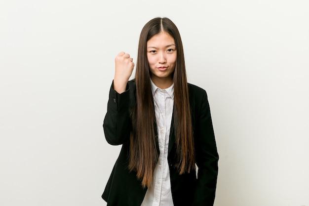 Giovane donna abbastanza cinese di affari che mostra il pugno alla macchina fotografica, espressione facciale aggressiva.