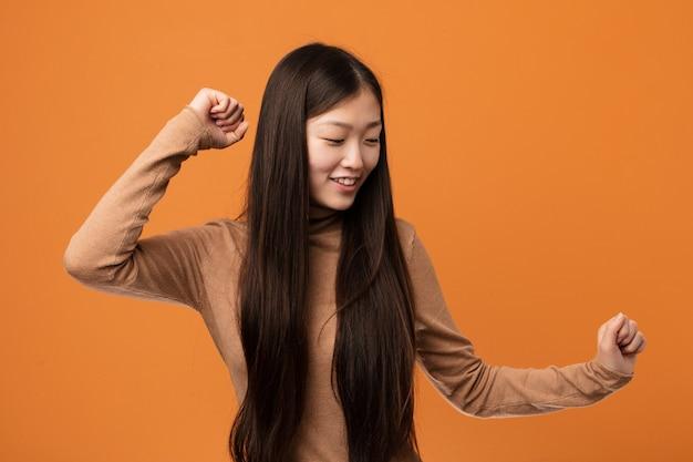Giovane donna abbastanza cinese ballando e divertendosi.