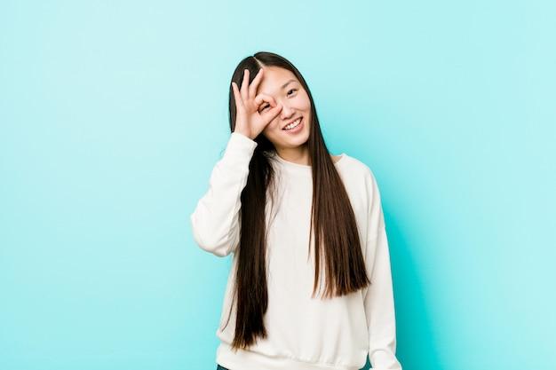 La giovane donna abbastanza cinese ha eccitato mantenendo il gesto giusto sull'occhio.