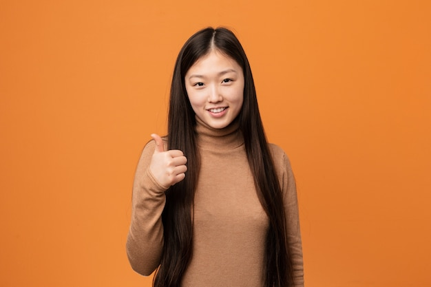 Giovane donna abbastanza cinese che sorride e che alza il pollice in su