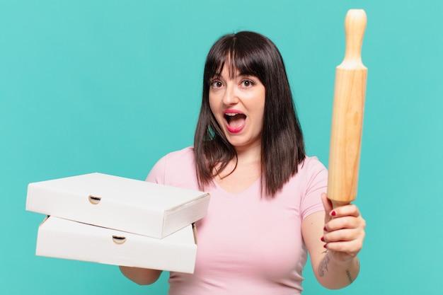 La giovane donna abbastanza formosa ha sorpreso l'espressione e tiene una pizza