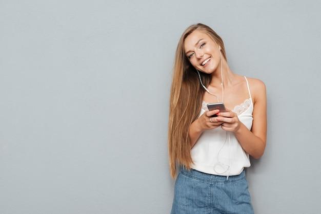 Giovane ragazza abbastanza carina con gli auricolari che ascolta musica e che tiene smartphone isolato su uno sfondo grigio