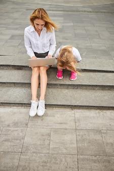 Giovane bella bambina in attesa della madre mentre è seduta sui gradini all'aperto