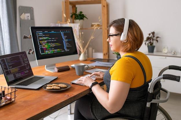Giovane sviluppatore di software piuttosto femminile in sedia a rotelle seduto dalla scrivania davanti al laptop e al monitor del computer mentre si lavora con i dati