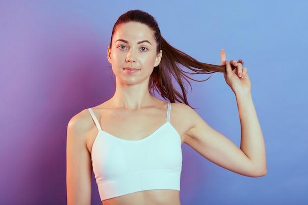 Giovane donna graziosa di forma fisica che tira la sua coda di cavallo da parte in posa isolata su sfondo colorato, guardando direttamente la telecamera, indossando canottiera bianca, ragazza sportiva dopo l'allenamento.