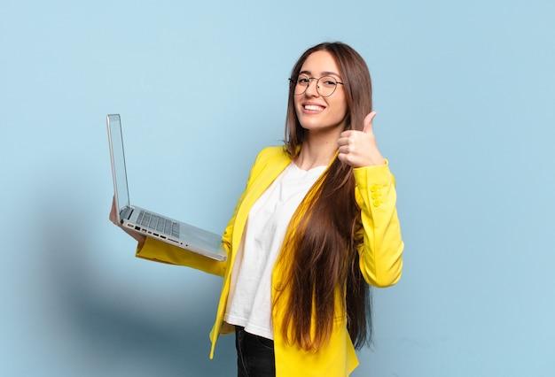 Giovane donna graziosa del libero professionista che tiene un computer portatile