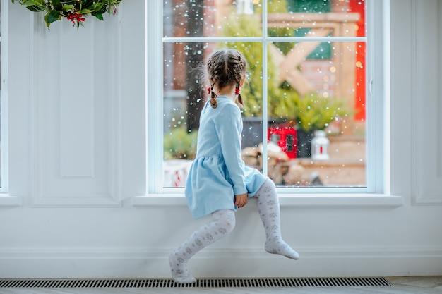 Giovane bella ragazza in abito invernale blu e collant seduto vicino alla grande finestra con il natale.