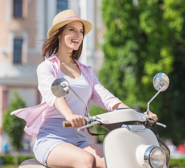 Giovane ragazza graziosa che guida motorino in città europea.