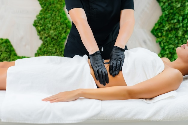 Una giovane ragazza carina si sta godendo un massaggio cosmetologico professionale presso la spa. cura del corpo. salone di bellezza.