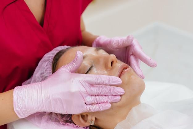 Una giovane ragazza carina si sta godendo un massaggio professionale alla testa presso la spa. cura del corpo. salone di bellezza.