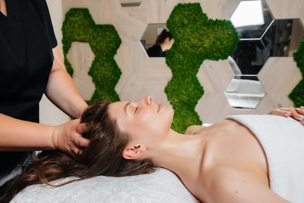 Una giovane ragazza carina si sta godendo un massaggio professionale alla testa presso la spa